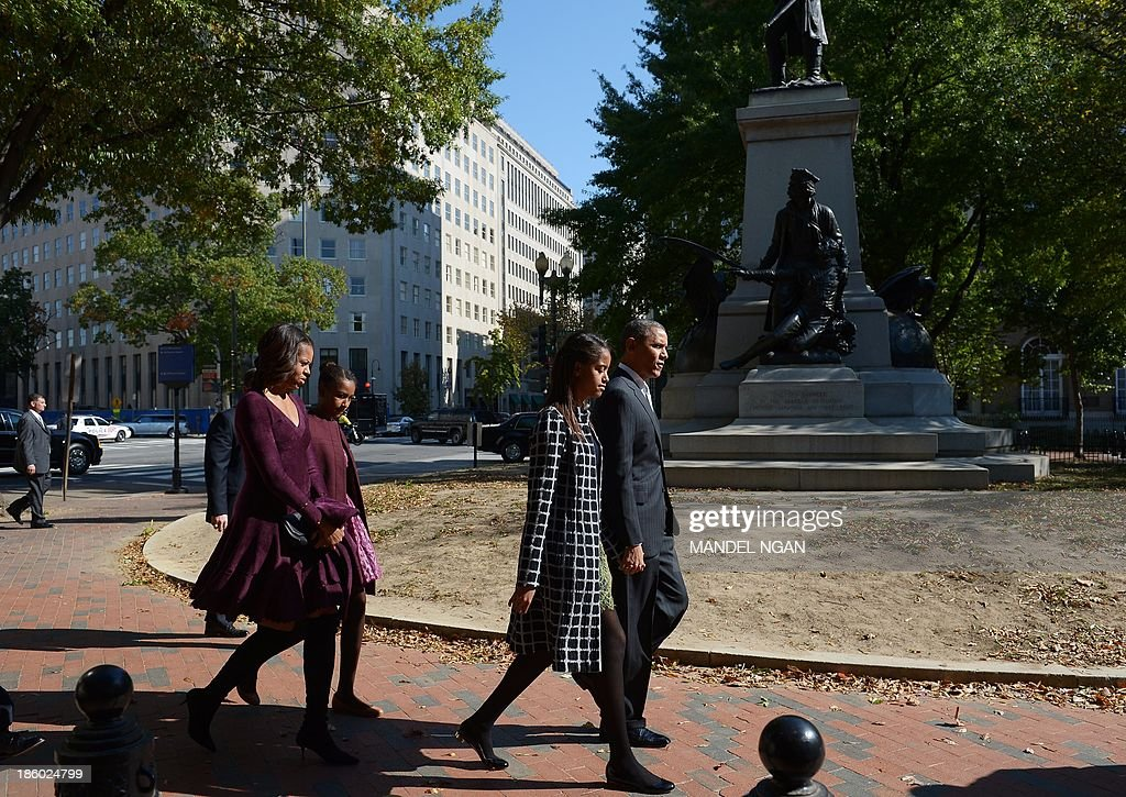 US President Barack Obama and First Lady Michelle Obama walk with daughters Malia (2nd R) and Sasha (2nd L) after attending Sunday services at Saint John's Episcopal Church October 27, 2013 in Washington, DC. AFP PHOTO/Mandel NGAN