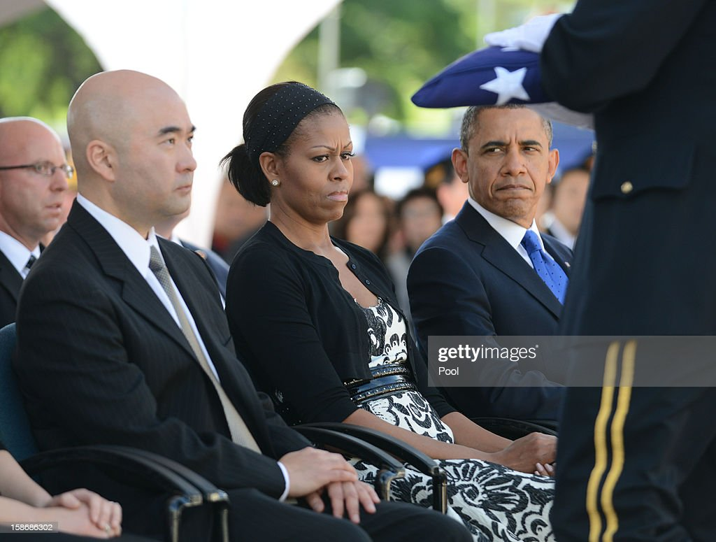 U.S. President Barack Obama and first lady Michelle Obama watch as an American flag is presented to Senator Daniel Inouye's son, Ken Inouye, during the funeral services at the National Memorial Cemetery of the Pacific December 23, 2012 in Honolulu, Hawaii. Senator Inouye was a Medal of Honor recipient and a United States Senator since 1963.