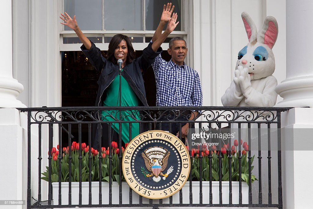 President Barack Obama and first lady Michelle Obama wave after they spoke to the crowd during the annual White House Easter Egg Roll on the South...