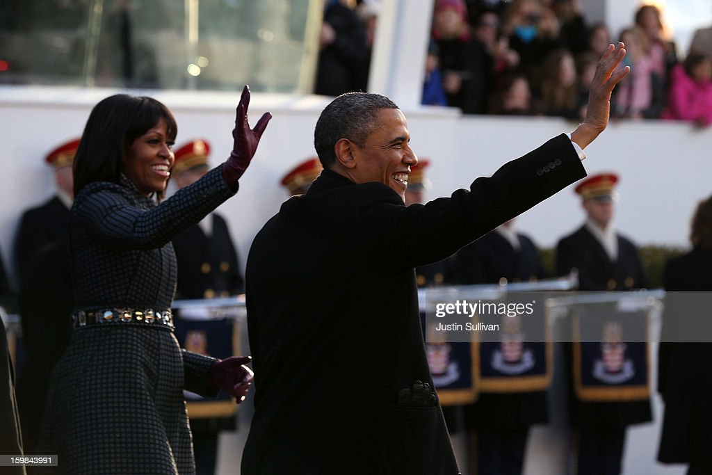 U.S. President Barack Obama and First lady Michelle Obama wave as the presidential inaugural parade winds through the nation's capital January 21, 2013 in Washington, DC. Barack Obama was re-elected for a second term as President of the United States.
