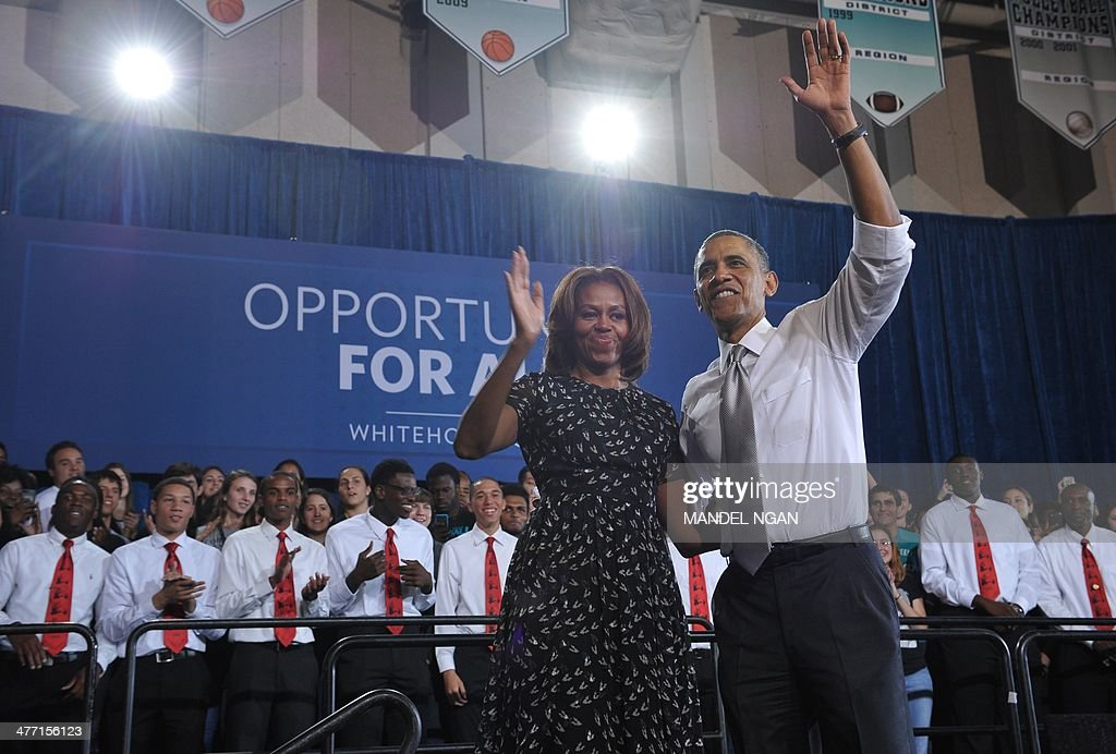 US President Barack Obama and First Lady Michelle Obama wave from the stage after Obama spoke at Coral Reef High School in Miami, Florida on March 7, 2014. AFP PHOTO/Mandel NGAN