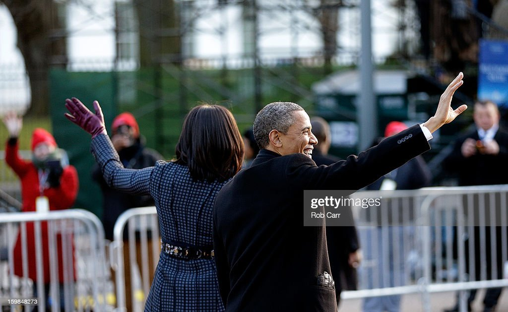 President Barack Obama and First lady Michelle Obama wave to onlookers as the presidential inaugural parade winds through the nation's capital January 21, 2013 in Washington, DC. Barack Obama was re-elected for a second term as President of the United States.