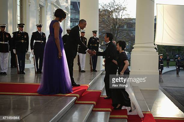 US President Barack Obama and first lady Michelle Obama welcome Japanese Prime Minister Shinzo Abe and his wife Akie Abe as they arrive for a state...