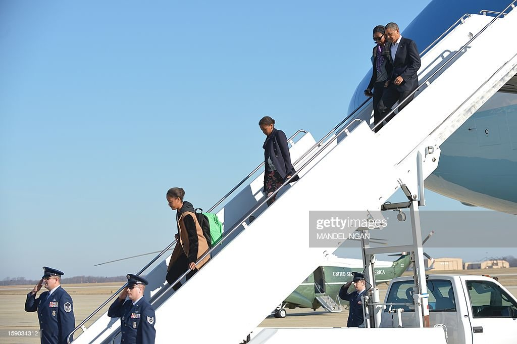 US President Barack Obama and First Lady Michelle Obama with daughters Malia (L) and Sasha step off Air Force One on January 6, 2013 upon arrival at Andrews Air Force Base in Maryland. Obama returned to Washington after finishing his vacation in Hawaii. AFP PHOTO/Mandel NGAN