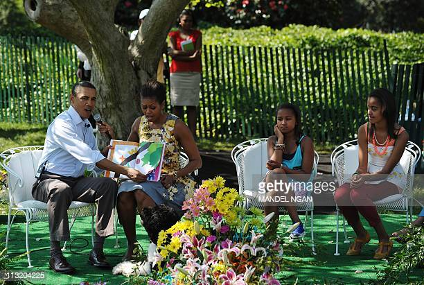 US President Barack Obama and First Lady Michelle read a book to children as their daughter Sasha and Malia look on during the annual Easter egg roll...