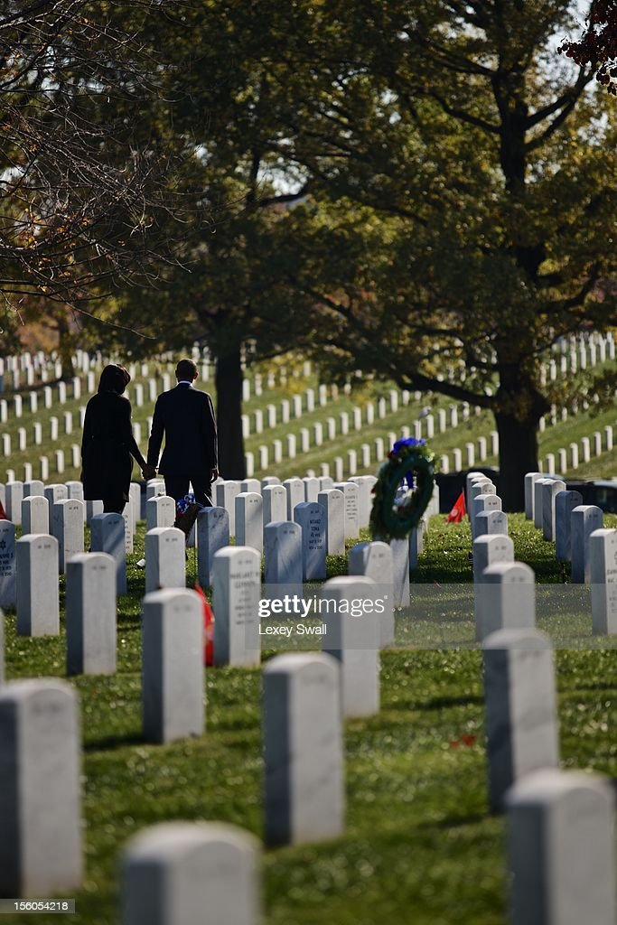 U.S. President Barack Obama and first lady Michelle walk through Arlington National Cemetery after greeting family members of fallen service men and women on Veteran's Day November 11, 2012 in Arlington, Virginia. Numerous events are under across the country to honor the nation's current and former service members.