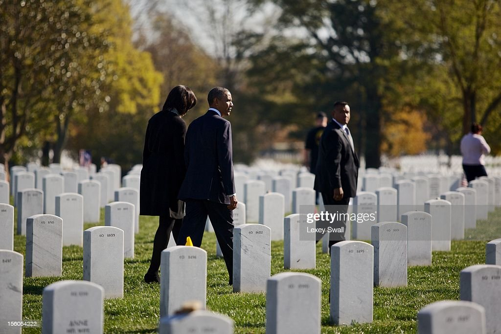 U.S. President <a gi-track='captionPersonalityLinkClicked' href=/galleries/search?phrase=Barack+Obama&family=editorial&specificpeople=203260 ng-click='$event.stopPropagation()'>Barack Obama</a> and first lady Michelle walk through Arlington National Cemetery after greeting family members of fallen service men and women on Veteran's Day November 11, 2012 in Arlington, Virginia. Numerous events are under across the country to honor the nation's current and former service members.