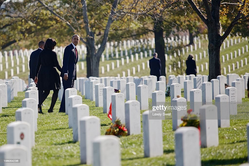 U.S. President Barack Obama and first lady, Michelle, walk through Arlington National Cemetery after greeting family members of fallen service men and women on Veteran's Day November 11, 2012 in Arlington, Virginia. Numerous events are under across the country to honor the nation's current and former service members.