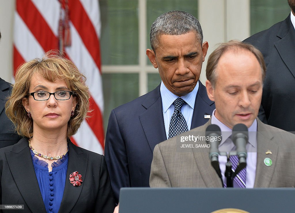 US President Barack Obama (C-back) and former lawmaker Gabrielle Giffords (L) listen as Mark Barden (R), father of a Newtown school shooting victim, speaks during a press conference at the Rose Garden of the White House in Washington, DC, on April 17, 2013. Obama on Wednesday slammed what he called a 'minority' in the US Senate for blocking legislation that would have expanded background checks on those seeking to buy guns. AFP PHOTO/Jewel Samad