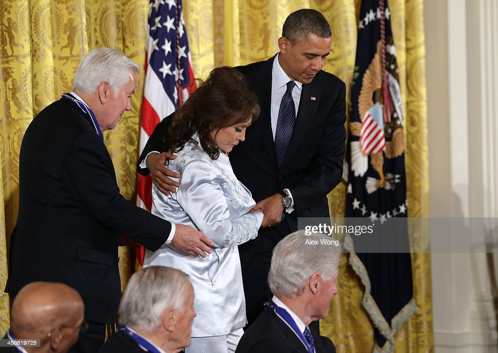 U.S. President Barack Obama (R) and former Senator Richard Lugar (R-IN) (L) assist country music legend Loretta Lynn (2nd L) on stage before she is awarded with the Presidential Medal of Freedom in the East Room at the White House on November 20, 2013 in Washington, DC. The Presidential Medal of Freedom is the nation's highest civilian honor, presented to individuals who have made meritorious contributions to the security or national interests of the United States, to world peace, or to cultural or other significant public or private endeavors.