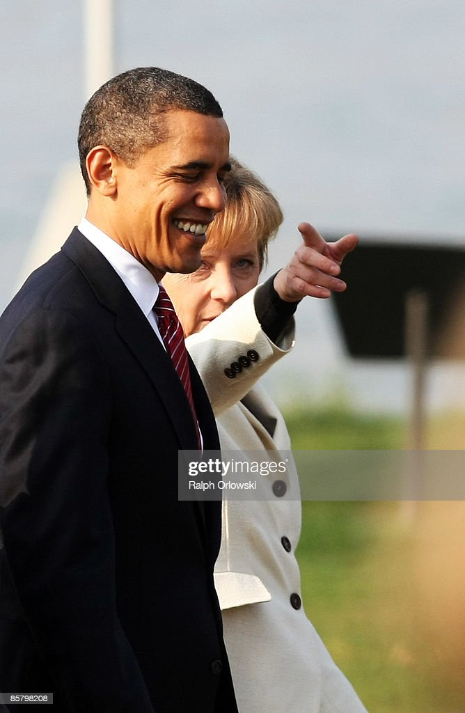 S President Barack Obama and German Chancellor Angela Merkel arrive for a military ceremony during the NATO summit at the Passerelle des DeuxRives on...