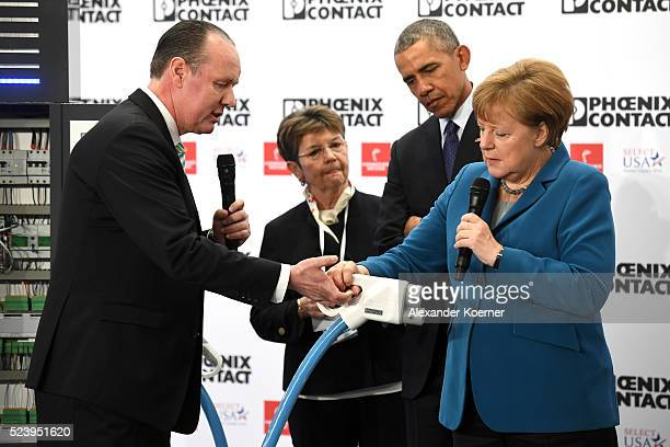 S President Barack Obama and German Chancellor Angela Merkel get an explanation by CEO of Phoenix Contact Frank Stuehrenberg at the Phoenix Contact...