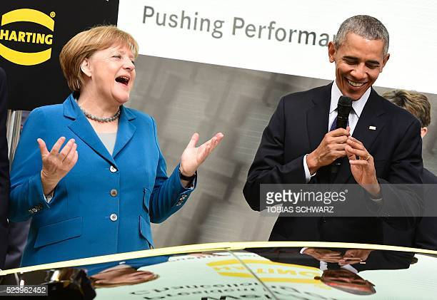 US President Barack Obama and German Chancellor Angela Merkel share a laugh at the booth of Harting technology group as they tour the Hanover...