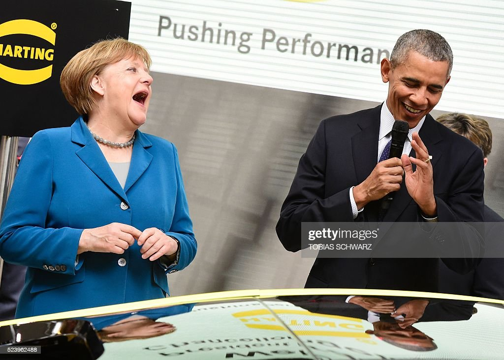 US President Barack Obama (R) and German Chancellor Angela Merkel share a laugh at the booth of Harting technology group as they tour the Hanover industrial Fair in Hanover, central Germany, on April 25, 2016. USA is partner country of the industrial fair Hannover Messe 2016 running from April 25 to April 29, 2016. / AFP / TOBIAS