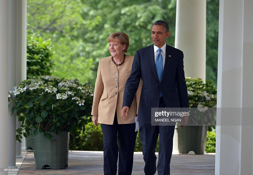 US President Barack Obama and German Chancellor Angela Merkel walk through the Colonnade on their way to a joint press conference in the Rose Garden of the White House on May 2, 2014 in Washington, DC. Obama welcomed Merkel to the White House Friday, seeking to secure united European backing for tougher sanctions on Russia's economy should the Kremlin escalate the crisis in Ukraine. AFP PHOTO/Mandel NGAN
