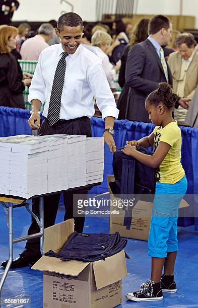US President Barack Obama and his daughter Sasha help volunteers and members of Congress stuff backpacks with books food and photographs of the first...