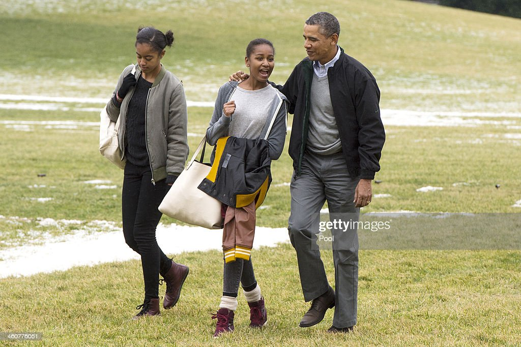 U.S. President Barack Obama (R) and his daughters Malia (L) and Sasha (C) walk across the South Lawn of the White House after arriving by Marine One January 5, 2014 in Washington, DC. Obama returns from a two-week holiday in Hawaii.