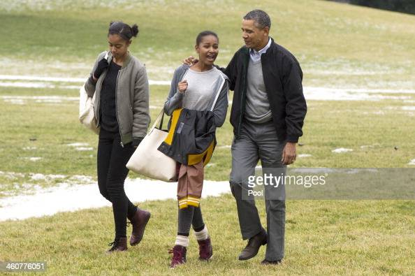 US President Barack Obama and his daughters Malia and Sasha walk across the South Lawn of the White House after arriving by Marine One January 5 2014...