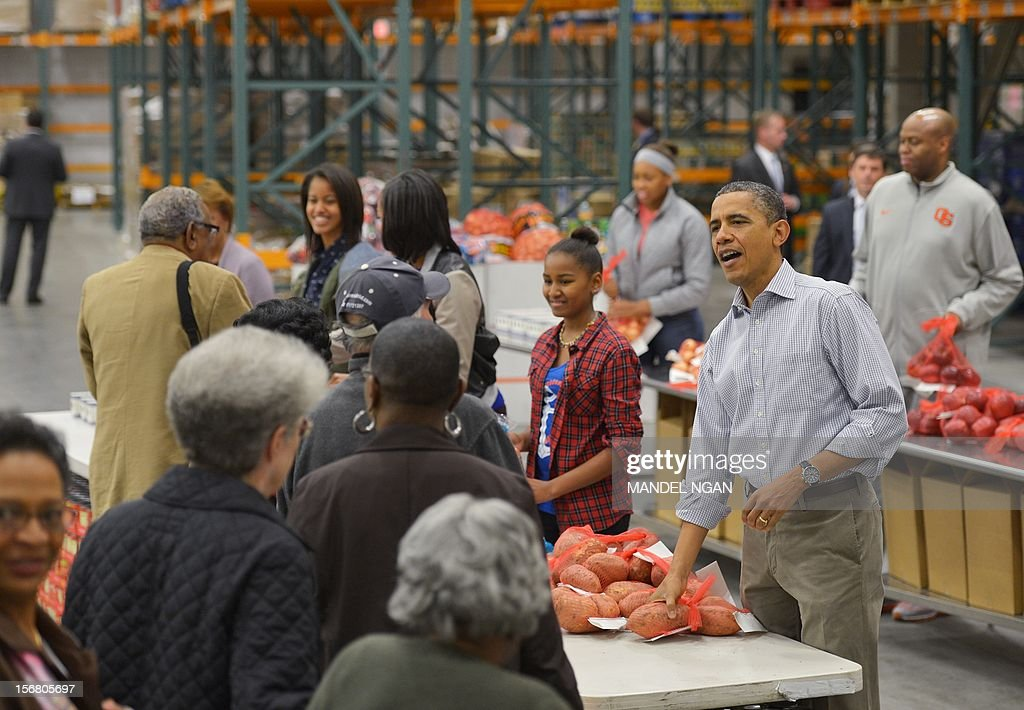 US President Barack Obama and his family distribute food items at the Capitol Area Food Bank on November 21, 2012, a day ahead of Thanksgiving, in Washington, DC. AFP PHOTO/Mandel NGAN