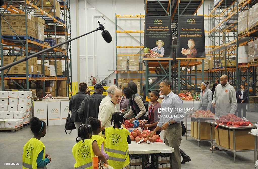 US President <a gi-track='captionPersonalityLinkClicked' href=/galleries/search?phrase=Barack+Obama&family=editorial&specificpeople=203260 ng-click='$event.stopPropagation()'>Barack Obama</a> and his family distribute food items at the Capitol Area Food Bank on November 21, 2012, a day ahead of Thanksgiving, in Washington, DC. AFP PHOTO/Mandel NGAN