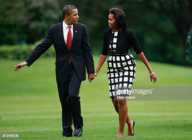 President Barack Obama and his wife first lady Michelle Obama walk on the south lawn after arriving back at the White House on October 2 2009 in...