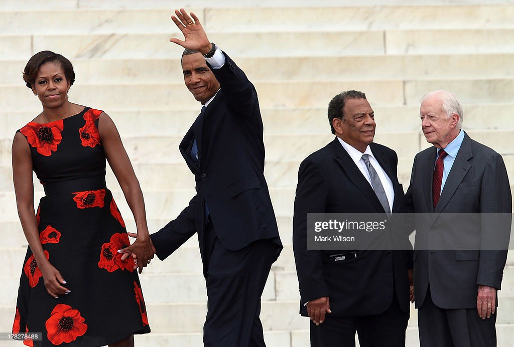 President Barack Obama (2nd-L) and his wife Michelle Obama hold hands as former U.S. President Jimmy Carter (R) and Andrew Young stand nearby during the ceremony to commemorate the 50th anniversary of the March on Washington for Jobs and Freedom August 28, 2013 in Washington, DC. It was 50 years ago today that Martin Luther King, Jr. delivered his 'I Have A Dream Speech' on the steps of the Lincoln Memorial.