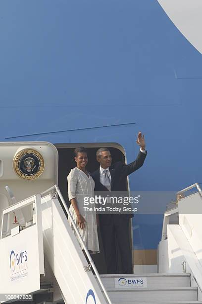 President Barack Obama and his wife Michelle Obama wave as they board Air Force One after their tour of India at the airport in New Delhi on Tuesday...