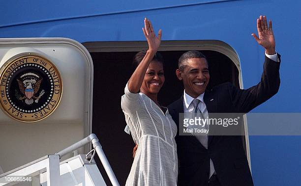 S President Barack Obama and his wife Michelle Obama wave as they board Air Force One as they leave for Indonesia at the end of their tour of India...