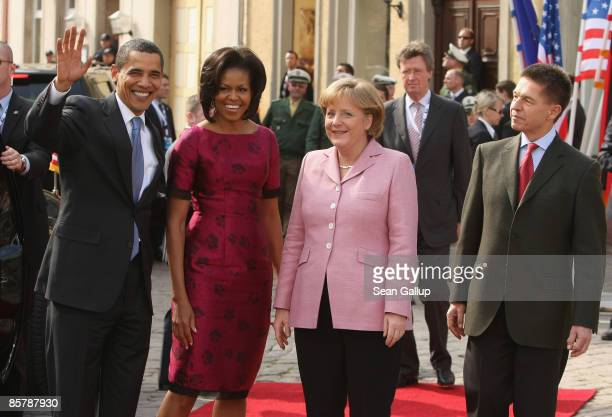 S President Barack Obama and his wife Michelle wave upon their arrival as German Chancellor Angela Merkel and her husband Joachim Sauer look on...