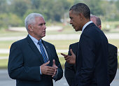US President Barack Obama and Indiana Governor Mike Pence chat at Evansville Regional Airport in Indiana upon Obama's arrival on October 3 2014 Obama...