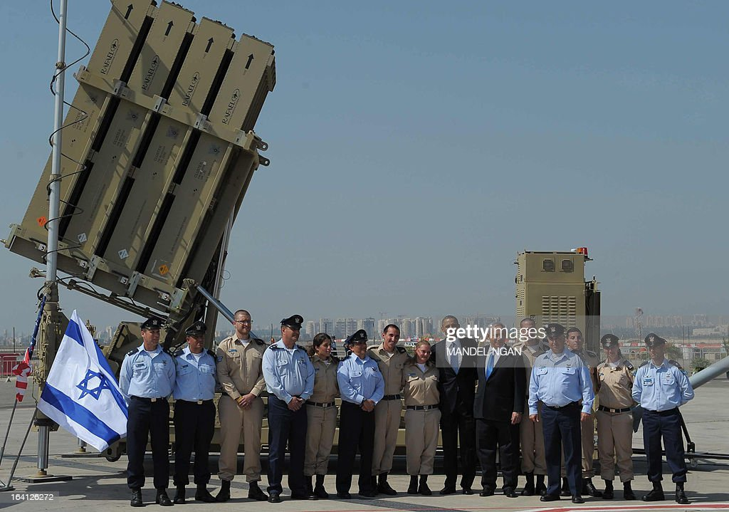 US President Barack Obama and Israeli Prime Minister Benjamin Netanyahu pose with military personnel next to a battery of Iron Dome, a short-range missile defence system, on March 20, 2013 at Ben Gurion International Airport near Tel Aviv. Obama landed in Israel for the first time as US president, on a mission to ease past tensions with his hosts and hoping to paper over differences on handling Iran's nuclear threat. AFP PHOTO/Mandel NGAN