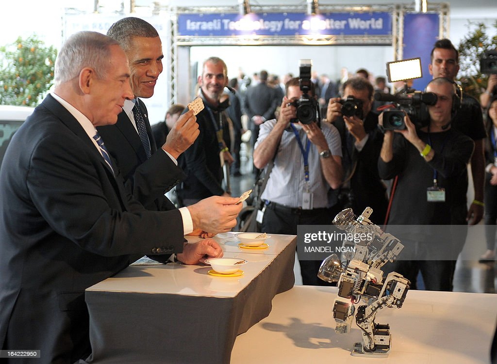 US President Barack Obama (R) and Israeli Prime Minister Benjamin Netanyahu (L) sample matza bread offered to them by small robots during a tour of a technology exposition at the Israel Museum in Jerusalem on Mach 21, 2013. Obama is on a three day official visit to the Israel, Palestinian territories and Jordan. AFP PHOTO/Mandel NGAN