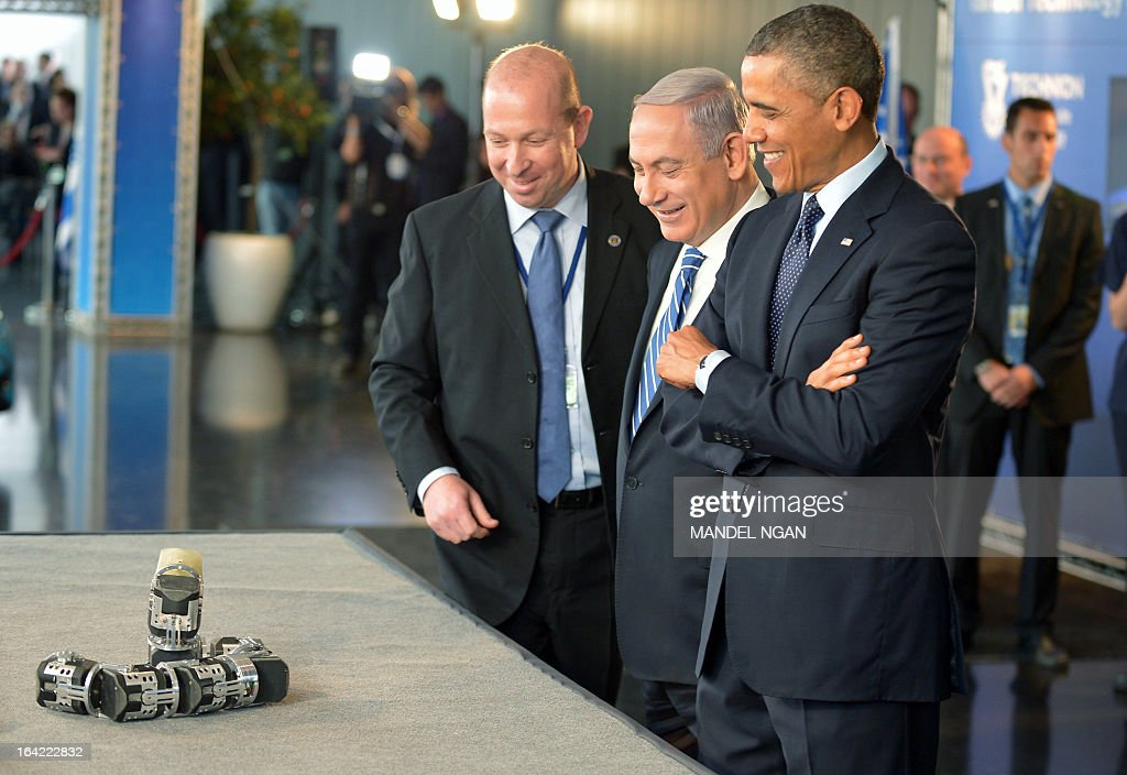 US President Barack Obama (R) and Israel's Prime Minister Benjamin Netanyahu (C) look at a snake-shaped robot which can be used in search and rescue operations during a tour of a technology exposition at the Israel Museum in Jerusalem on Mach 21, 2013. Obama is on a three day official visit to the Israel, Palestinian territories and Jordan. AFP PHOTO/Mandel NGAN