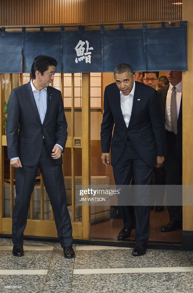 US President Barack Obama (R) and Japanese Prime Minister Shinzo Abe (L) depart after a private dinner at Sukiyabashi Jiro restaurant in Tokyo on April 23, 2014. Obama landed in Tokyo on April 23 to launch an Asian tour dedicated to reinvigorating his policy of 'rebalancing' US foreign policy towards a dynamic Asia. Sukiyabashi Jiro's less-than-plush surroundings notwithstanding, it is the proud possessor of three Michelin stars, and people flock to pay a minimum $300 for 20 pieces of sushi chosen by the 88-year-old patron, Jiro Ono. AFP PHOTO / Jim WATSON