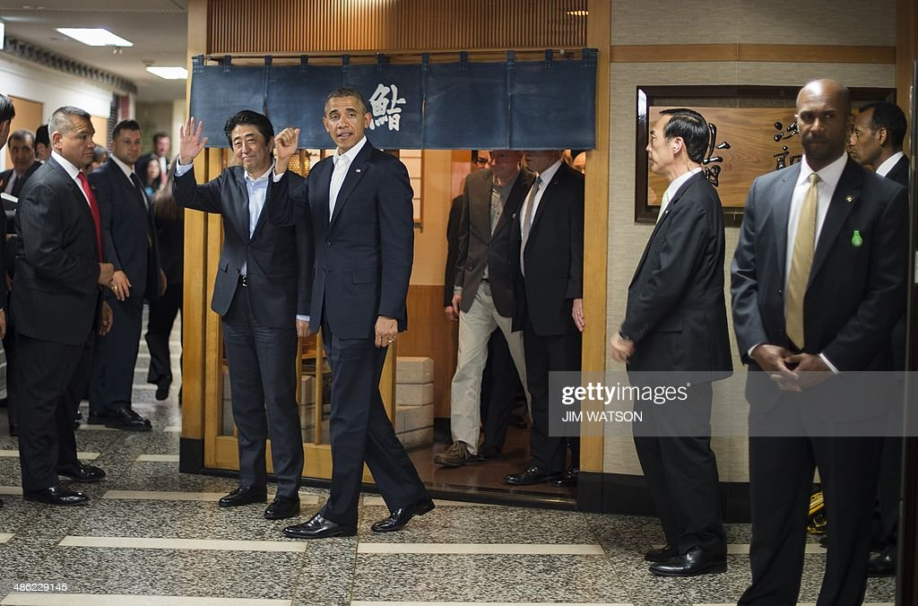 US President Barack Obama (C) and Japanese Prime Minister Shinzo Abe (2nd L) depart after a private dinner at Sukiyabashi Jiro restaurant in Tokyo on April 23, 2014. Obama landed in Tokyo on April 23 to launch an Asian tour dedicated to reinvigorating his policy of 'rebalancing' US foreign policy towards a dynamic Asia. Sukiyabashi Jiro's less-than-plush surroundings notwithstanding, it is the proud possessor of three Michelin stars, and people flock to pay a minimum $300 for 20 pieces of sushi chosen by the 88-year-old patron, Jiro Ono. AFP PHOTO / Jim WATSON