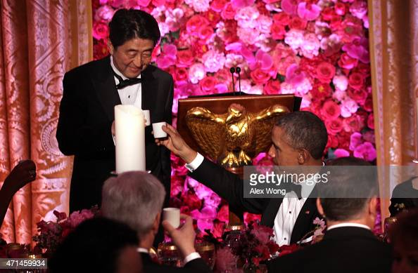 US President Barack Obama and Japanese Prime Minister Shinzo Abe participate in a toast with sake during a state dinner at the East Room of the White...
