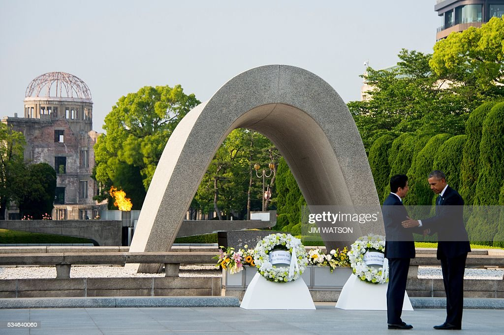 US President Barack Obama (R) and Japanese Prime Minister Shinzo Abe shake hands after laying wreaths at the Hiroshima Peace Memorial Park in Hiroshima on May 27, 2016. Obama on May 27 paid moving tribute to victims of the world's first nuclear attack. WATSON