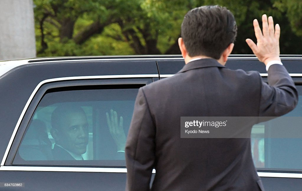 U.S. President Barack Obama (inside a car) and Japanese Prime Minister Shinzo Abe wave to each other after the president made a historic visit to the Peace Memorial Park in Hiroshima on May 27, 2016.
