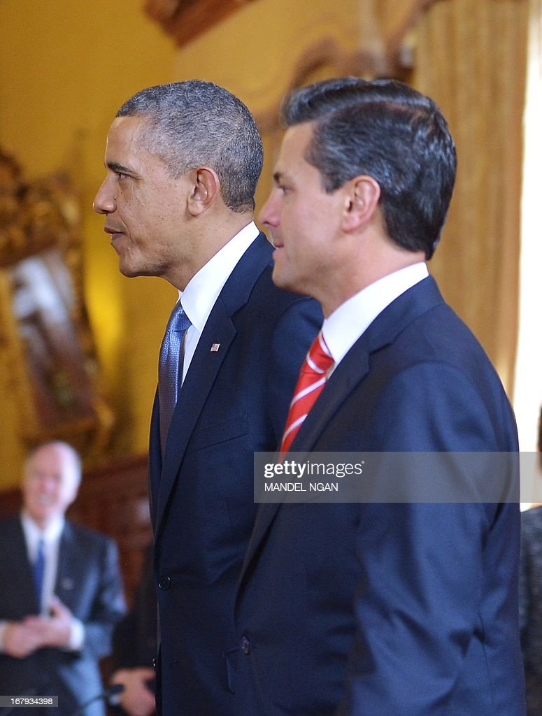 US President Barack Obama (L) and Mexican President Enrique Pena Nieto make their way to their seats for a bilateral meeting on May 2, 2013 at the Palacio Nacional in Mexico City. Obama landed in Mexico on Thursday at the start of a three-day trip that will also take him to Costa Rica, with trade, US immigration reform and the drug war high on the agenda. The runways of Mexico City's international airport closed for half an hour to let Air Force One land, and Obama was scheduled to head to the historic National Palace downtown for talks with Mexican President Enrique Pena Nieto. AFP PHOTO / Mandel NGAN