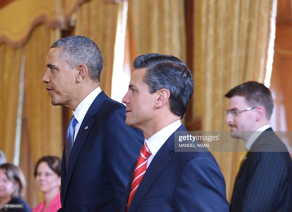 US President Barack Obama (L) and Mexican President Enrique Pena Nieto make their way to their seats for a bilateral meeting on May 2, 2013 at the Palacio Nacional in Mexico City. Obama landed in Mexico on Thursday at the start of a three-day trip that will also take him to Costa Rica, with trade, US immigration reform and the drug war high on the agenda. The runways of Mexico City's international airport closed for half an hour to let Air Force One land, and Obama was scheduled to head to the historic National Palace downtown for talks with Mexican President Enrique Pena Nieto.AFP PHOTO/Mandel NGAN