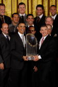 S President Barack Obama and New York Yankees Manager Joe Girardi hold the Major League Baseball Commissioner's Trophy while posing for photographs...