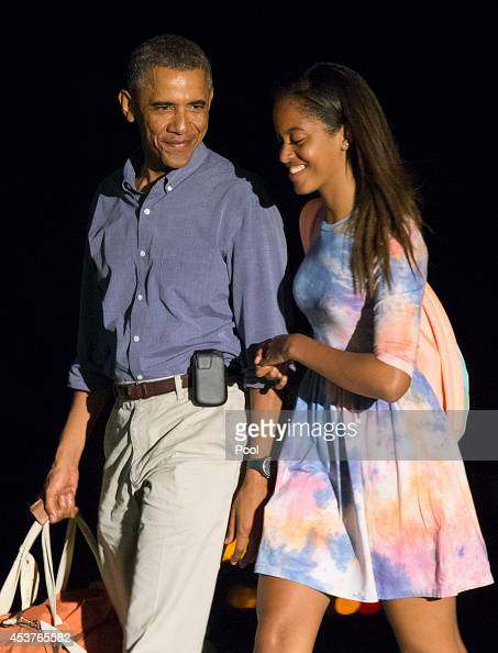 President Barack Obama and oldest daughter Malia return to the White House on August 17 2014 in Washington DC The president is taking a break from...