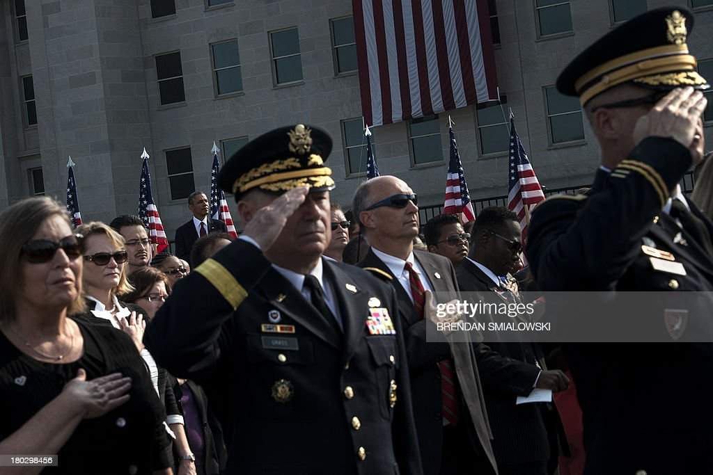 US President Barack Obama(L-rear) and others salute during the playing of the US National Anthem during a memorial service at the National 9/11 Pentagon Memorial September 11, 2013 in Washington, DC. Obama, Hagel and others attend the event to mark the 12th anniversary of terries attacks on the Pentagon and the World Trade Center. AFP PHOTO Brendan SMIALOWSKI