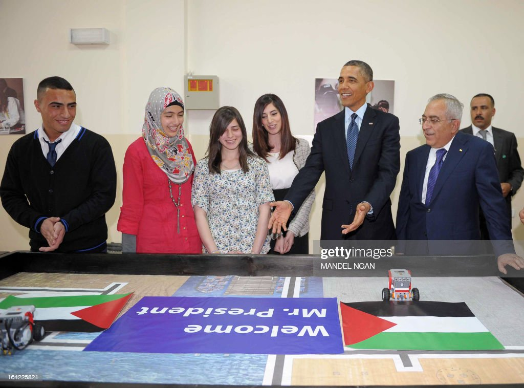 US President Barack Obama (2R) and Palestinian prime minister Salam Fayyad (R) are greeted by a welcome message unveiled by small robots during a visit to the al-Bireh Youth Center in the West Bank city of Ramallah on March 21, 2013. Obama expressed full backing for the establishment of a Palestinian state following talks in Ramallah with Palestinian president Mahmud Abbas. AFP PHOTO/Mandel NGAN