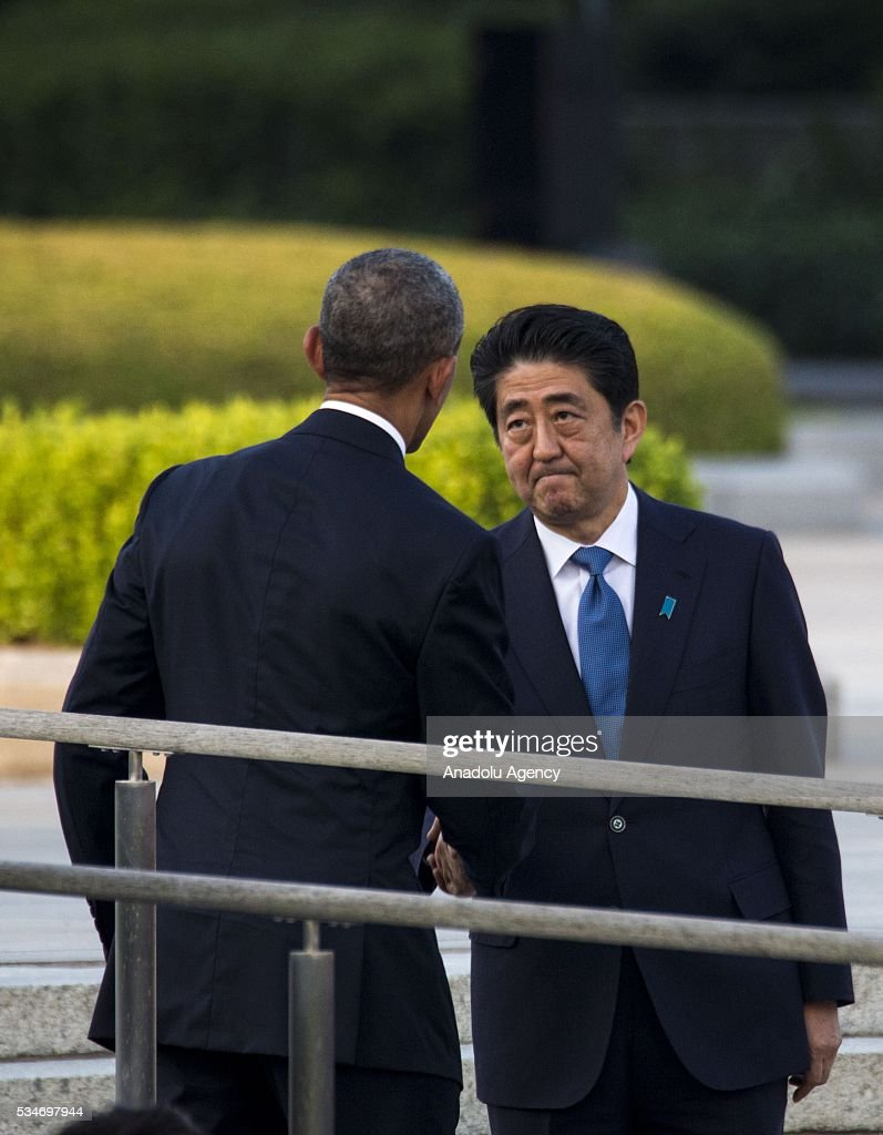 U.S. President Barack Obama (L) and Prime Minister Shinzo Abe (R) shake hands during their visit to the cenotaph at Hiroshima Peace Memorial Park to respect to the families of victims, killed by an atomic bomb in Hiroshima, Japan on May 27, 2016. US President Barack Obama is the first American president, visiting Hiroshima after United States of America dropped Atomic bomb in Hiroshima on August 6, 1945.