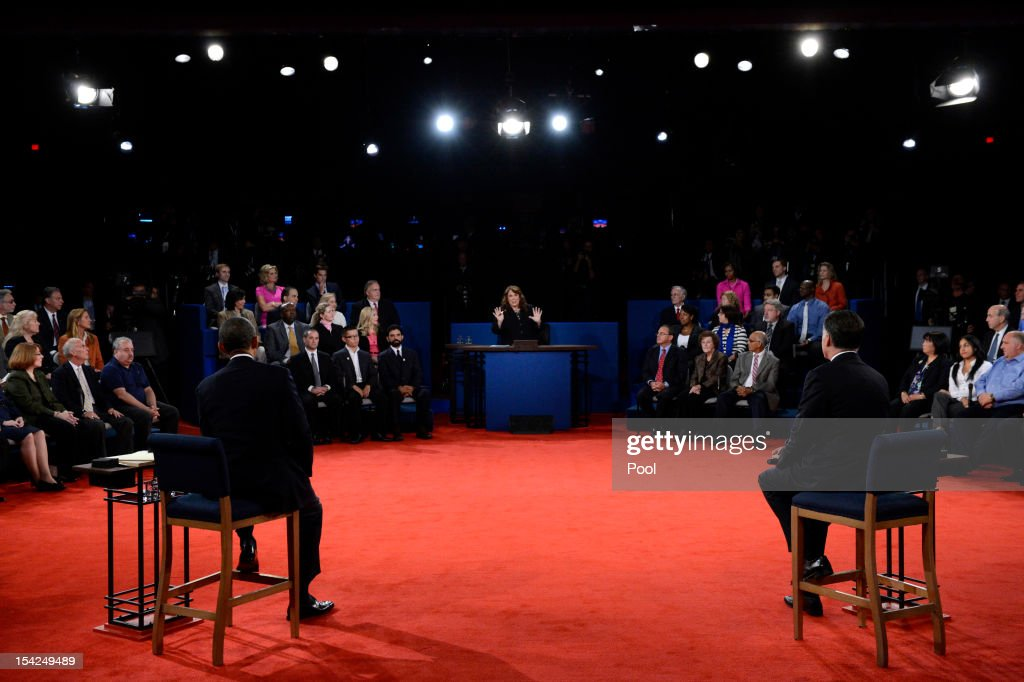 S President Barack Obama and Republican presidential candidate Mitt Romney listen to moderator Candy Crowley during a town hall style debate at...