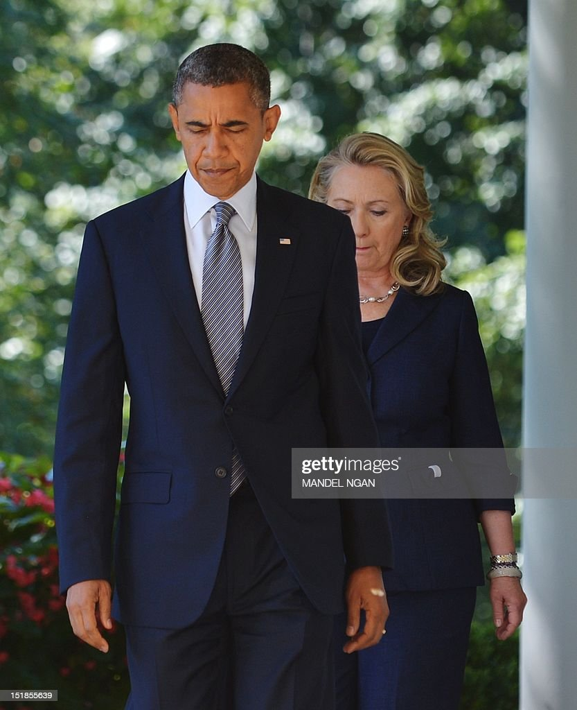 US President Barack Obama and Secretary of State Hillary Clinton make their way through the Colonnade to deliver a statement in the Rose Garden of the White House on September 12, 2012 in Washington, DC. Obama spoke on the attack on the US consulate in Benghazi, Libya which left US Ambassador Chris Stevens and three other American dead. AFP PHOTO/Mandel NGAN