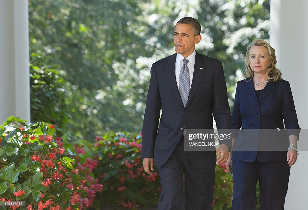 US President Barack Obama and Secretary of State Hillary Clinton make their way through the Colonnade to deliver a statement in the Rose Garden of the White House September 12, 2012 in Washington, DC. Obama spoke on the attack on the US consulate in Benghazi, Libya which left US Ambassador Chris Stevens and three other American dead. AFP PHOTO/Mandel NGAN