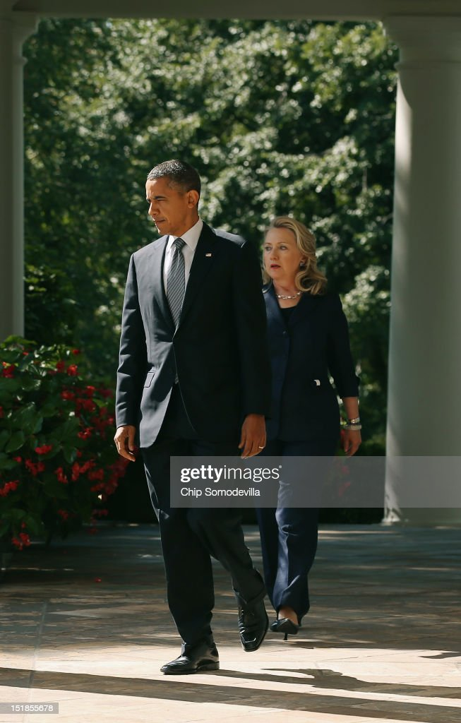 S President Barack Obama and Secretary of State Hillary Clinton walk into the Rose Garden before Obama makes a statement about the death of US...