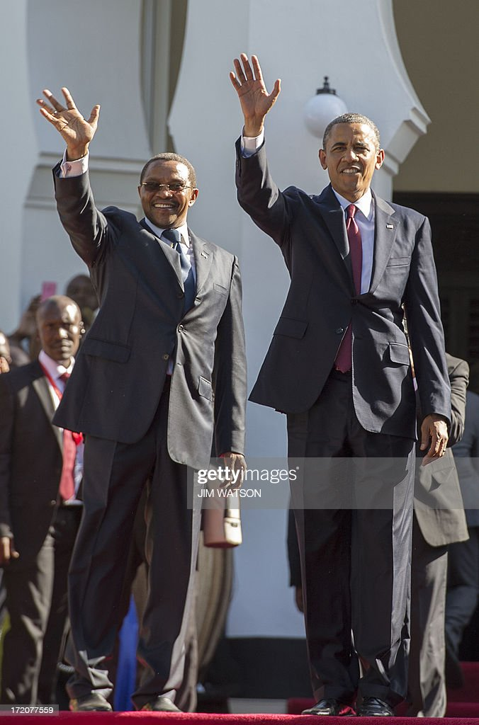 President Barack Obama (R) and Tanzanian President Jakaya Kikwete wave to the crowd as they participate in an arrival ceremony at the State House in Dar es Salaam, on July 1, 2013. Obama flew into Tanzania on the last leg of his three-nation Africa tour on Monday. AFP PHOTO/JIM WATSON